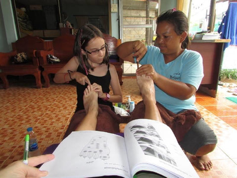 Our 9 year old daughter taking a foot massage class in the North of Thailand.