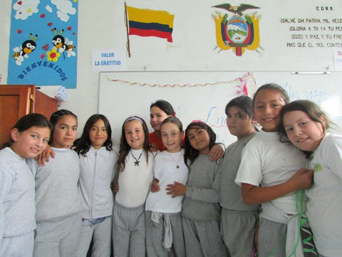 Our 9 year old daughter standing in the middle of her school friends in the classroom in Ecuador