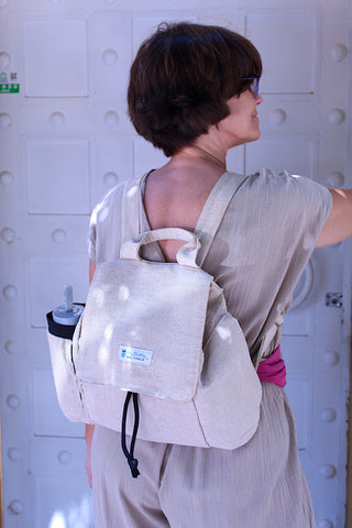 A woman wearing a beige cotton outfit is wearing the backpack in front of a house.