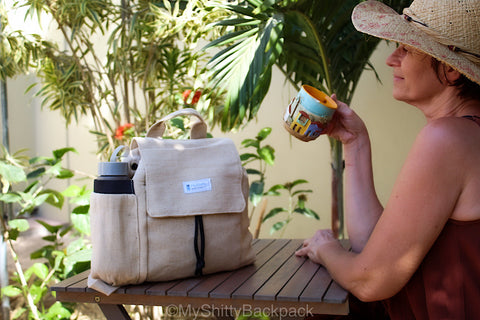 Woman is sitting at a teak table sipping tea, with the backpack on top of the table. the background is palm trees.