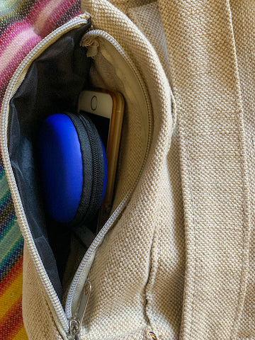 Photo showing the side zipper pocket open with a smartphone and earbud case in it.
