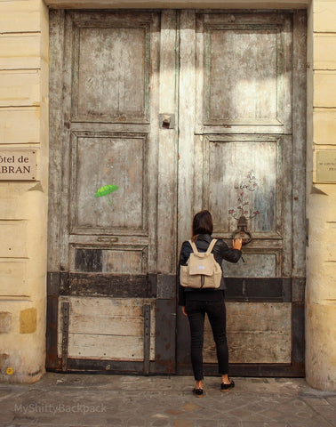 A young woman is knocking at a huge wooden door while wearing the backpack
