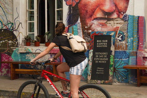 A young woman is riding her bicycle while wearing the backpack