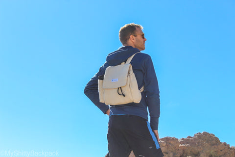 A man is standing on a rock on a background of blue sky while wearing the backpack