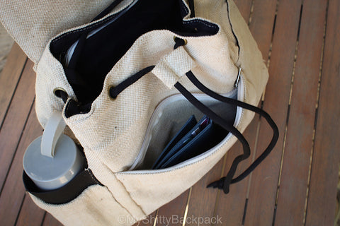 The flap of the backpack is open, showing the main compartment and the front zipper pocket open