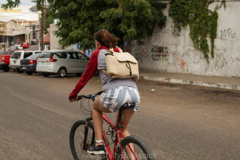 A young woman is riding a bicycle while wearing the backpack