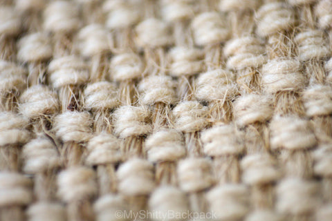 This photo shows a close-up of the same material, the vertical darker strands being the hemp fibers, and the horizontal lighter colored strands being the cotton fibers