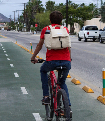 A young man is riding his bicycle in a street while wearing the backpack
