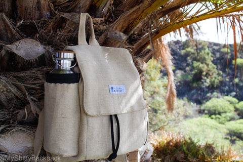 The backpack is shown hanging from a palm tree leaf. A large metal water bottle is inside the side water bottle holder