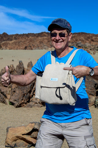 A middle-aged man is weary the backpack in the front, with a desert background