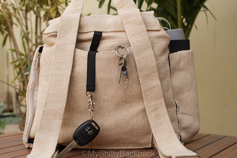 Photo showing a set of car keys and a set of house keys clipped to the 2 hooks in the back of the backpack