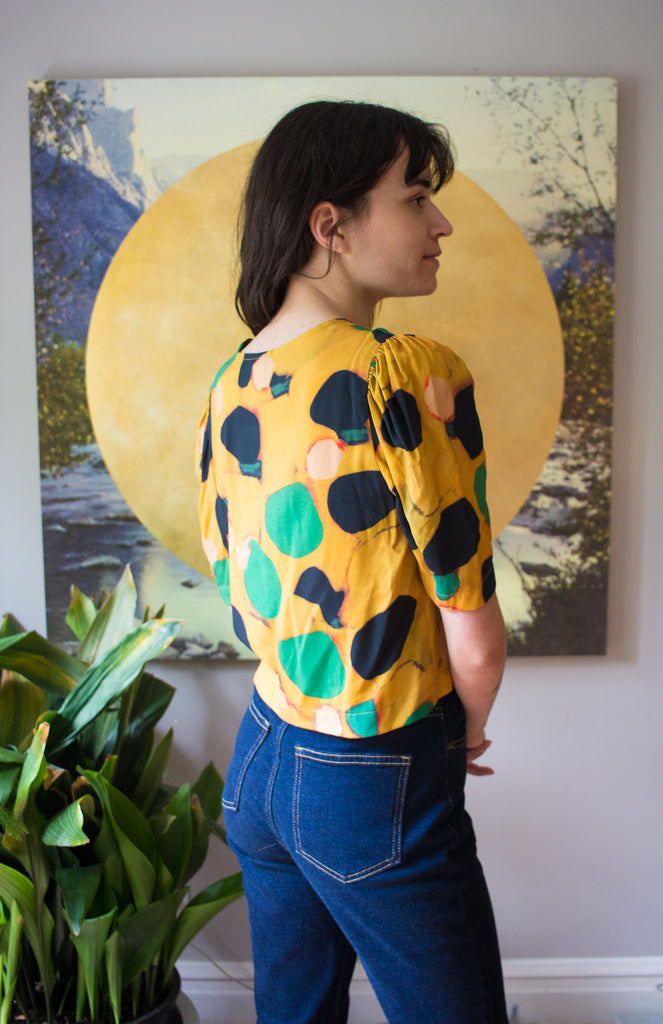Eve Gravel Clothing Montreal Bright Lights Top Klimt Pattern. Viscose Square Cut Blouse with Gathered Half Puff Sleeves and Bright Multi Coloured Watercolour Pattern.