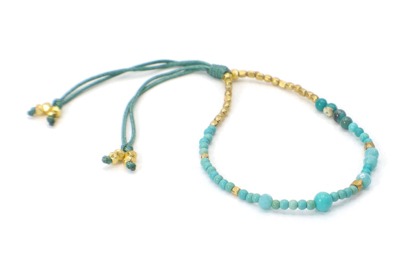 This is a single strand gemstone bracelet. Perfect for someone with a natural style. This is made with turquoise, chrysocolla, and Czech glass. They are combined with gold beads. This bracelet is handmade with love in Thailand. This is a Fair Trade Product.