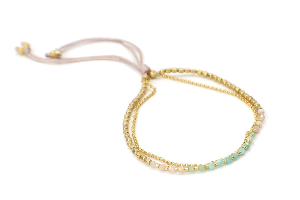 This beautiful ombre palette of aquamarine, emerald, and pink quartz gemstones are combined with brass beads.  It is offset with a gold plated chain.