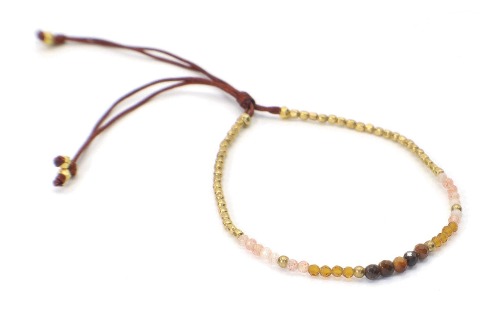 This single strand minimalist gemstone bracelet is perfect for stacking with the rest of your collection. The faceted tiger eye, and strawberry quartz, goes perfectly with the amber crystals and gold beads. This bracelet is handmade with love in Thailand. This is a Fair Trade Product.