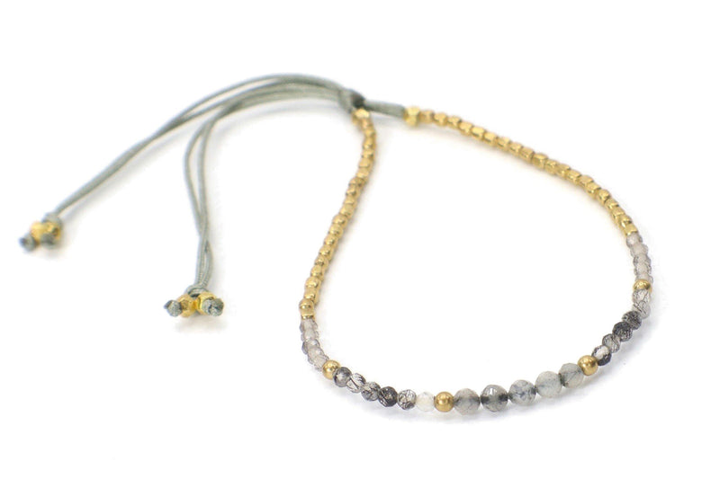 This single strand minimalist gemstone bracelet is perfect for stacking with the rest of your collection. The faceted smokey quarts go perfectly with the smoky crystals and gold beads. This bracelet is handmade with love in Thailand. This is a Fair Trade Product.