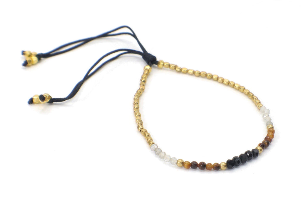 Celeste Bracelet - Black | Brown. This single strand minimalist gemstone bracelet is perfect for stacking with the rest of your collection. The faceted onyx, tiger eye gemstones and smoky crystal quartz are combined with gold beads. This bracelet is handmade with love in Thailand. This is a Fair Trade Product.