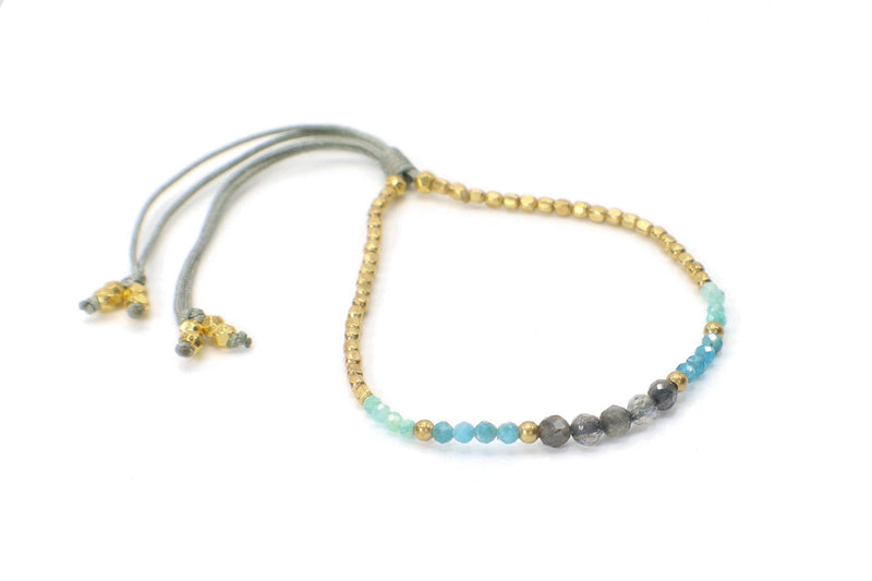 Celeste Bracelet - Gray | Turquoise. This single strand minimalist gemstone bracelet is perfect for stacking with the rest of your collection. The faceted smokey quartz, apatite, and aquamarine gemstone are combined with gold beads. This bracelet is handmade with love in Thailand. This is a Fair Trade Product.