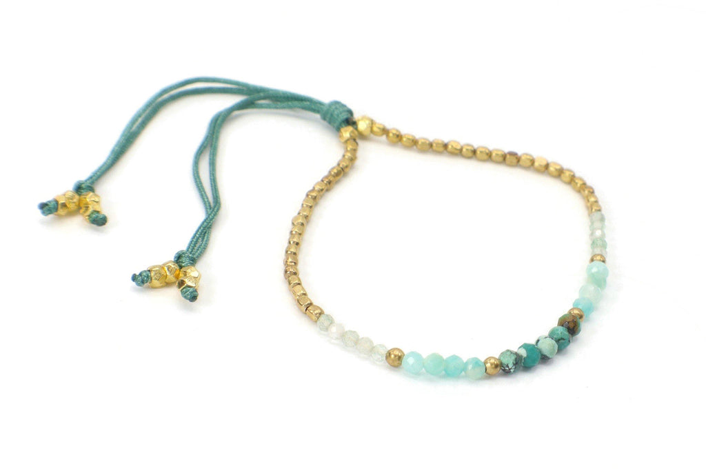 Celeste Bracelet - Light Blue | Turquoise. This single strand minimalist gemstone bracelet is perfect for stacking with the rest of your collection. The faceted African turquoise, aquamarine, gemstones, and crystals are combined with gold beads. This bracelet is handmade with love in Thailand. This is a Fair Trade Product.