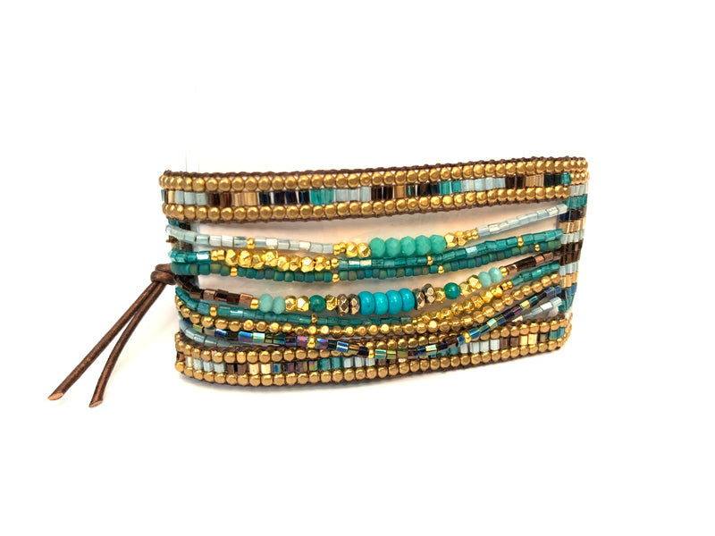 Micaela Bracelet in turquoise and brown. It is a cuff bracelet with multiple strands in the center, giving it a layered feel with in one piece.