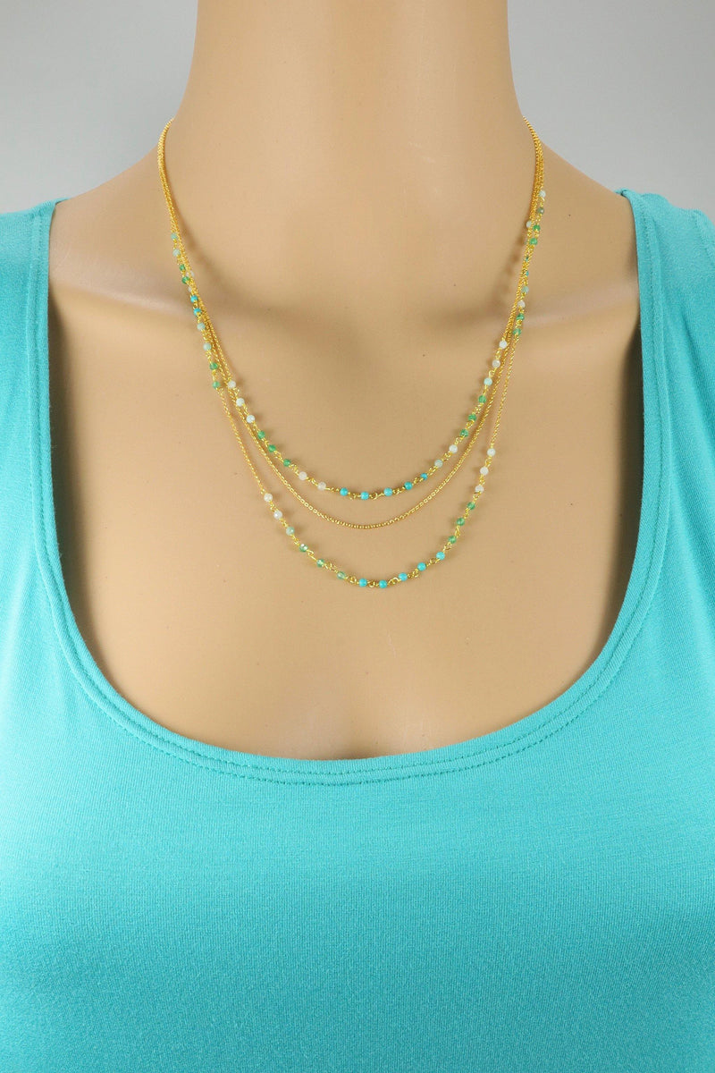 The Francesca necklace is a triple-layered faceted gemstone necklace. The first and third layers are rosary chain and the second layer is a gold chain. This necklace is handmade with turquoise, aquamarine, and emerald gemstones.