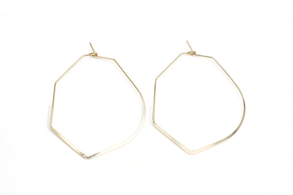 This is a unique take on a hexagon style earring. It features a rounded edge triangle shape with an angled bottom edge. This is a handmade, fairtrade product from Thailand.