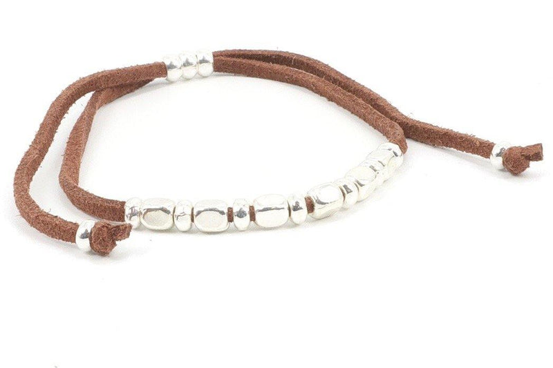 This is a silver beaded bracelet on suede leather. The silver beads contrast with the brown leather, giving an easy but versatile look. Silver is elegant while leather is all-terrain. This leather bracelet is perfect for stacking with other bracelets. Wear it with your favorite pair of jeans, and combine it with our Silver Heart Necklace for a unique style