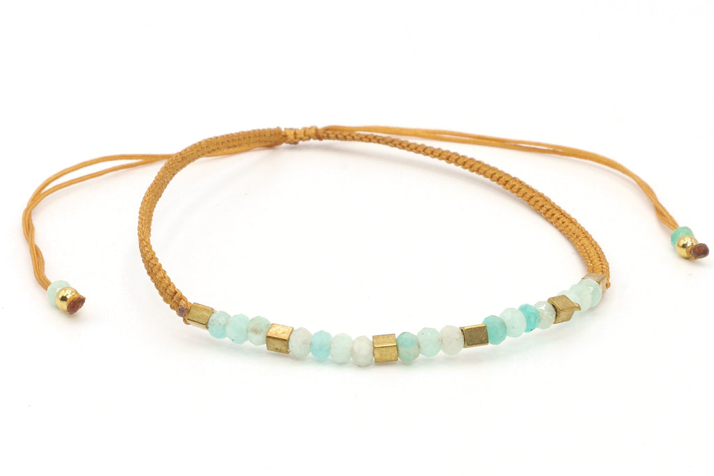 This is a beaded bracelet with aquamarine and brass square beads. Aquamarine is the birthstone for anyone born in March. The healing properties in aquamarine reduce stress and clarify perception. The beautiful light blue hues in aquamarine are totally relaxing. The brass square beads and the honey-colored silk cord, contrast with the gemstone color. This beaded bracelet is perfect for stacking with other bracelets.
