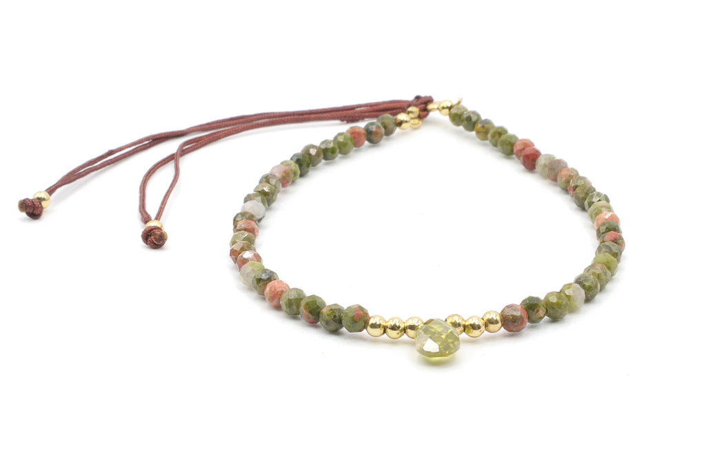 This is a unikite gemstone bracelet with 18k gold plated beads. There is a faceted peridot stone as a centerpiece. The bracelet is so easy to wear because the silk cord just slides open to adjust perfectly to any sized wrist.