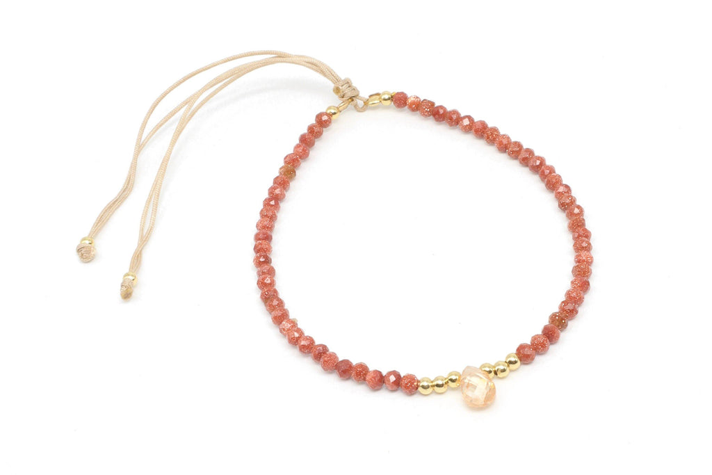 This is a sandstone gemstone bracelet with a faceted citrine teardrop. It features faceted gemstones and 18k gold plated beads on a sand-colored silk cord. This gemstone bracelet is dainty, minimalist, and understated. It is handmade and durable.