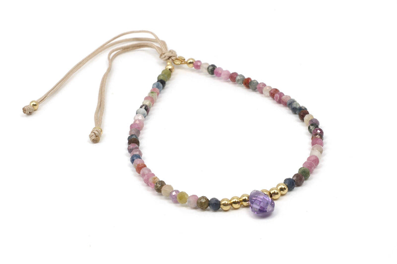 This is a tourmaline bracelet with a faceted amethyst teardrop as a centerpiece. This unique gemstone bracelet features18k gold plated beads and faceted gemstones. This dainty, minimalist bracelet is beaded on a silk cord, making it both casual and classy. It has a slide cord fitting so that it will easily adjust perfectly to your size.