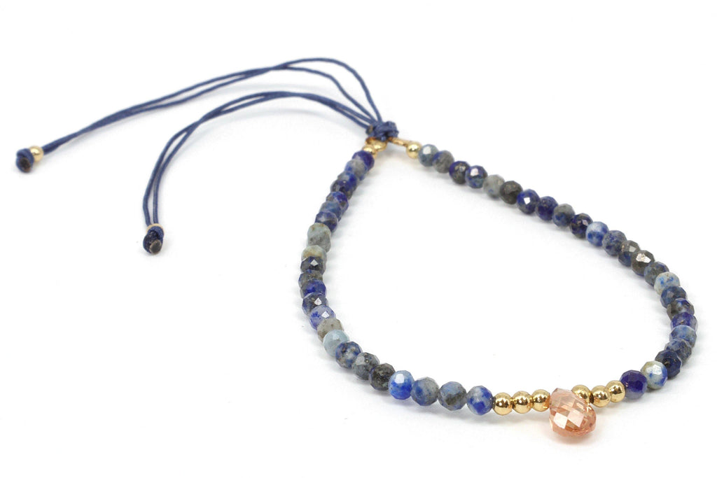 This is sodalite beaded bracelet with a faceted citrine teardrop center piece. It features natural gemstones, 18K gold anti tarnish beads, and silk cord. The bracelet pops because there is a contrast between the blue color in the sodalite gemstone and the bright sparkle in the citrine teardrop. Wear this with your favorite blue jeans and your sexy honey-colored leather gladiator sandals and go for a simple boho-chic look.