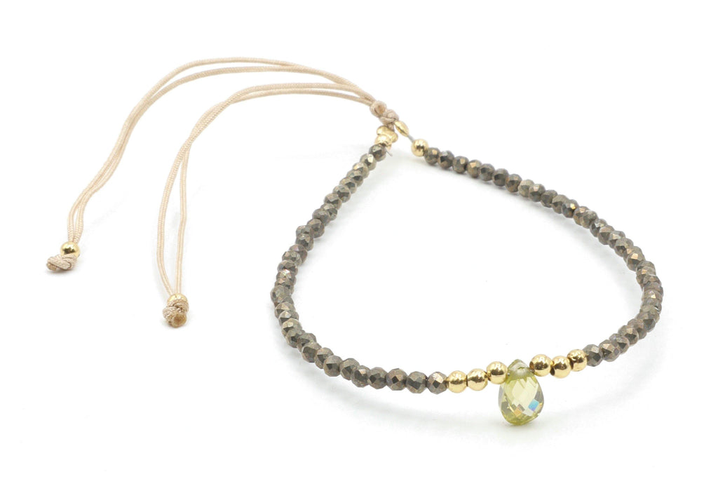 This is a pyrite gemstone bracelet with a faceted peridot teardrop on a silk cord. The pyrite and peridot colors make this bracelet so versatile. The colors are mixed are rich and soft. It's a little bit hippy, a little bit elegant. This will be your go-to piece!