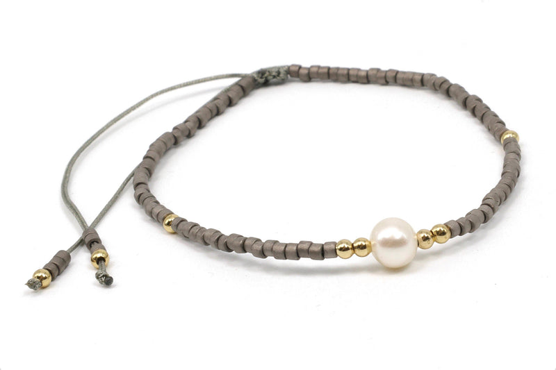 This is a Miyuki seed bead bracelet with a freshwater pearl, on a gray silk cord. Miyuki seed beads are uniform glass cylinders with flat ends that contrasts with the irregular shape of a natural freshwater pearl. The dark gray color contrasts perfectly with the pearl. This bracelet has an elegant, yet casual feel. Dress up a pair of jeans and create a neutral color pallet. This can also be worn with a dark red top. Try it with our Big Hoodie Sleeveless Top