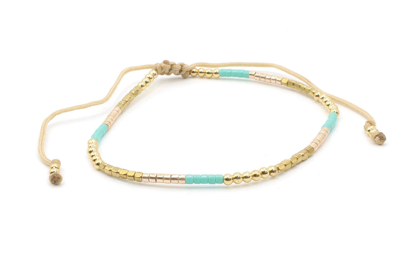 This is a beaded bracelet, made with turquoise and gold Miyuki seed beads on a cream silk cord. It has a fun, light casual feel to it, making it a great piece to add to leather or turquoise bracelet collection. Try it with the Long Maxi Dress in Light Blue.