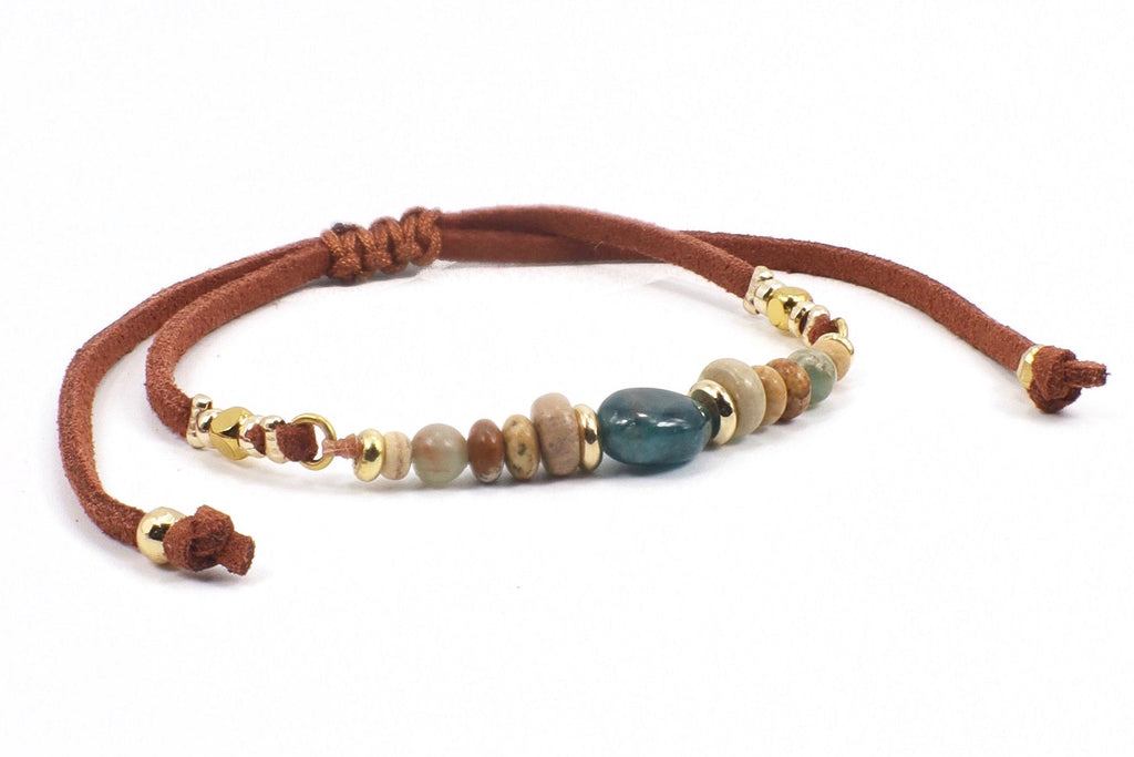 This is a bohemian gemstone leather bracelet. The bracelet has a carefree bohemian look. This unique, artsy bracelet, features beautiful earthy colors, like in the sky, the earth, and the sea. It is made with apatite, serpentine jasper, wood coco, and gold plated and copper beads. The blue apatite gemstone color is vibrant and powerful and matches perfectly with its complementary color of rust.