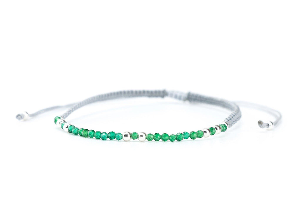 This is a minimalist bracelet made with faeted emerald gemstones on a gray silk cord.  It features a slide knot to make this bracelet adjustable and easy to put on.  This emerald stone is all about the heart.  When you wear this emerald bracelet, you may notice yourself feeling more unconditional love and compassion.  It is said that the emerald stone provides harmony, peace, balance and a feeling of mental clarity.     May is the month of the emerald birthstone.  Its vibrant green is like Spring.  This is