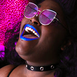 Blue-lipsticked model smiles widely while wearing shades with purple lenses and a black leather choker with silver grommets.