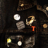 A black denim vest is adorned with many pins. Among them is a Q-Words pin, a vintage gold crab pin, some letters and others.