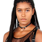 Model with long braids stares directly into camera while wearing a mesh top, a chest harness, and a thin black leather o-ring choker.