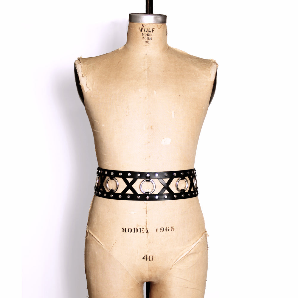 Double strap belt with leather X's and metal O's between the two belts. Belt shown on a dress form.