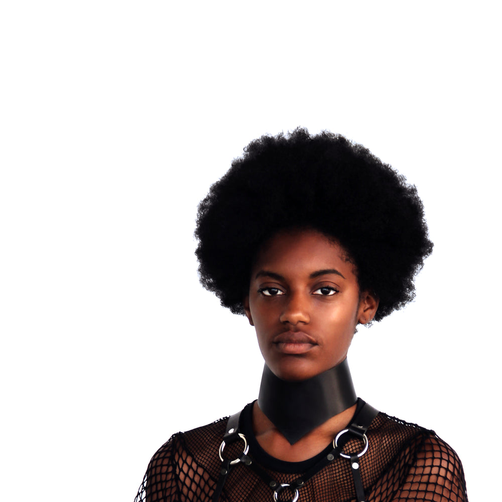 Model with an afro stares directly into the camera while wearing a posture collar, mesh top and leather harness.