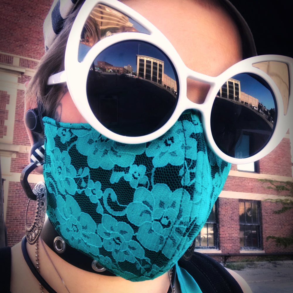Model wearing a lace mask downtown paired with oversized pointed sunglasses.