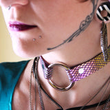 Close up of model's neck wearing a mermaid scale o-ring choker. Iridescent scales shine magenta/yellow/teal in the light.