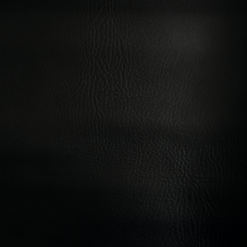 Black faux leather swatch shows leather grain texture of material.