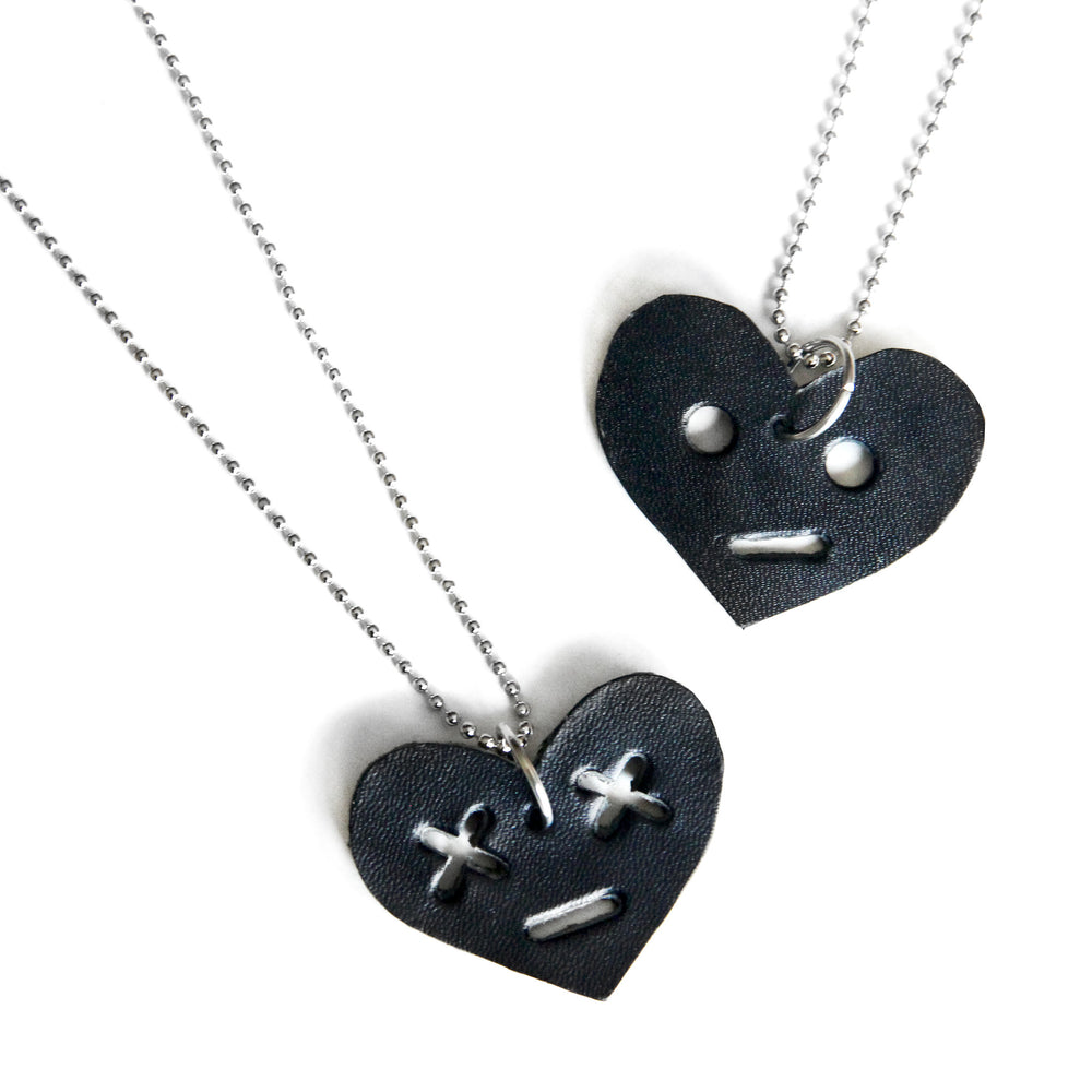 Leather heart necklaces with face. One with circle eyes, one with x eyes