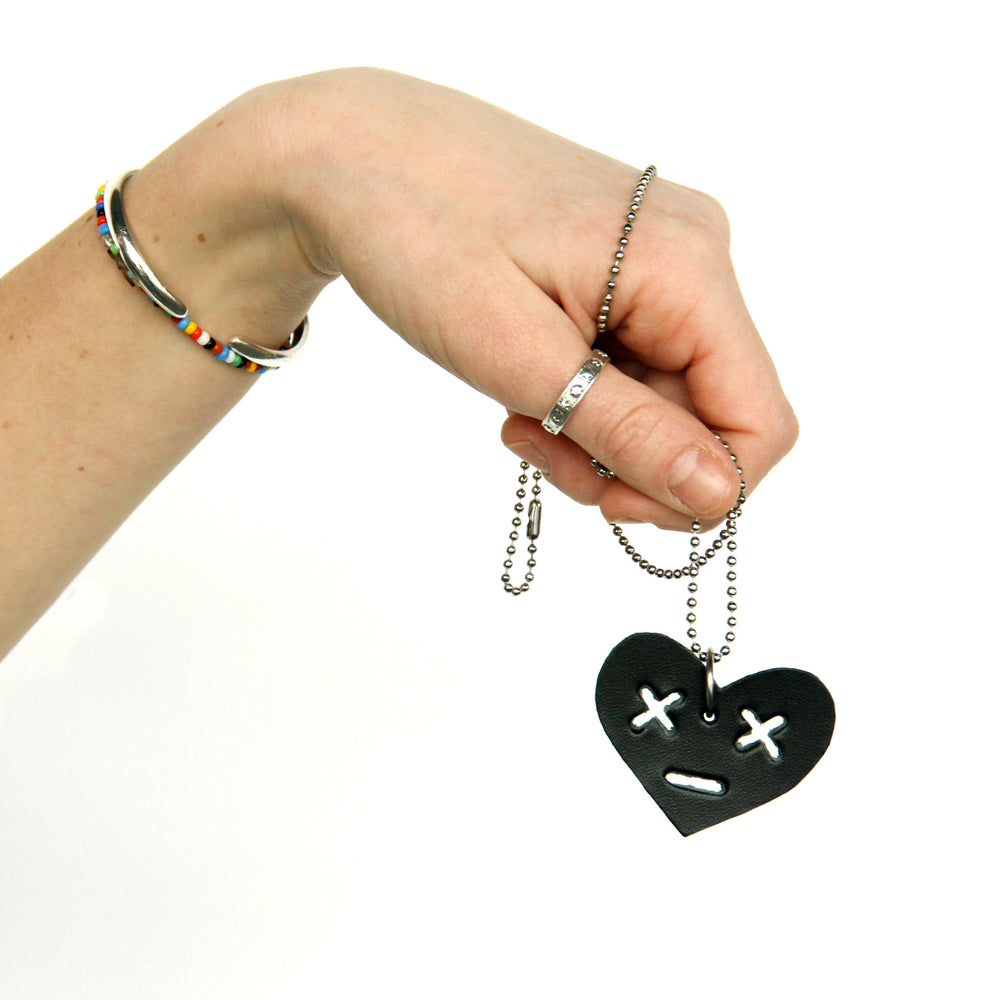 Model holding leather heart necklace