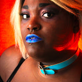 Model in a bold blue lipstick stares right into camera. They wear a teal basic buckle choker with silver hardware.