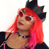 Model wearing crazy glitter glasses and a wig models a black leather crown, a pink chest harness, and a violet o-ring choker.