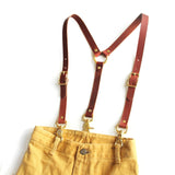 Chestnut brown leather high-waisted suspenders, with swivel trigger clips and brass hardware on pants